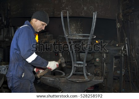 Blacksmith works in a small smithy