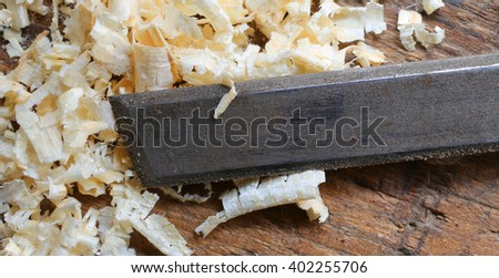 Blade of a sharpened chisel and sawdust in the Carpenter's Workbench - stock photo