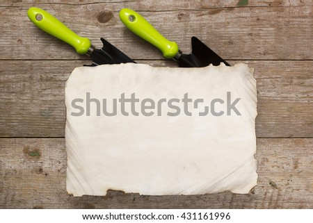 Blades for gardening and a blank sheet of paper on a wooden table - stock photo