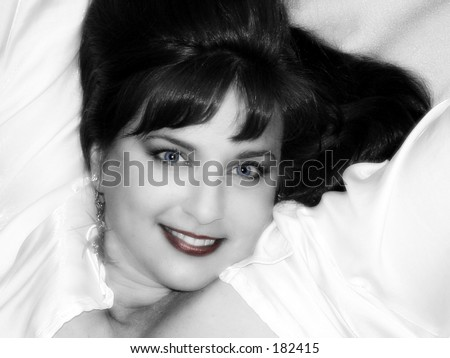 Blakc and white tinted photo of woman reclining in white satin shirt - stock photo