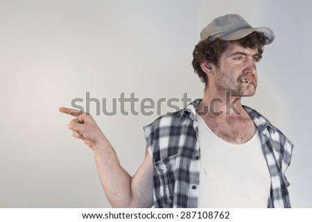 Blaming redneck bosses everyone around as he smokes his cigarette - stock photo