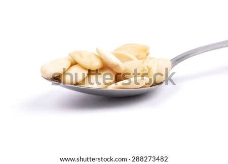 Blanched almonds on spoon - stock photo