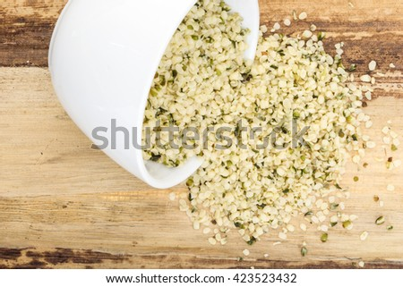 Blanched hemp seeds in bowl, on wooden background - stock photo