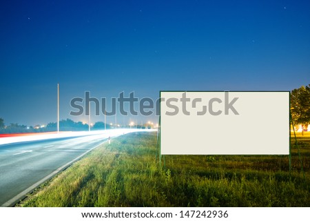 Blank advertising billboard by the busy road at night  - stock photo