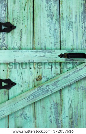 Blank antique mint green rustic wood door with black iron hinges and handle - stock photo