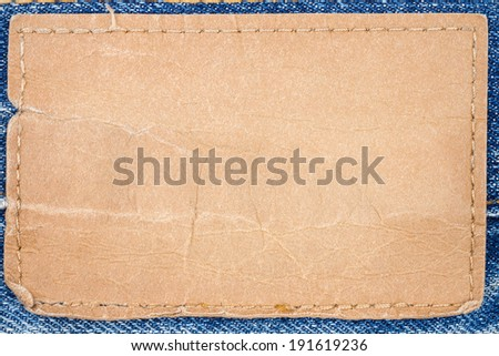 Blank artificial leather jeans label sewed on a blue jeans - stock photo