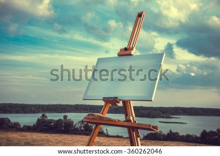 Blank artist canvas rests on a easel on lake landscape, retro styled photo. - stock photo