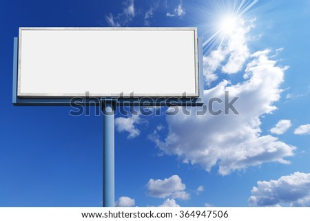 Blank Billboard Against a Blue Sky / Big empty billboard with blue pole on a blue sky with clouds and sun rays - stock photo