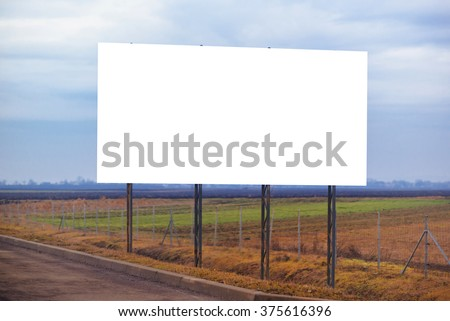 Blank billboard hoarding by the roadway, copy space for graphic design mock up, retro toned image. - stock photo