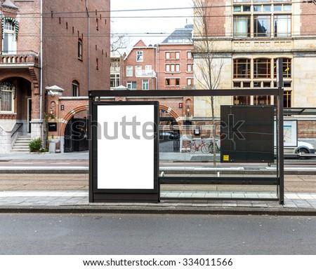 Blank billboard on bus stop on a roadside in european town - stock photo