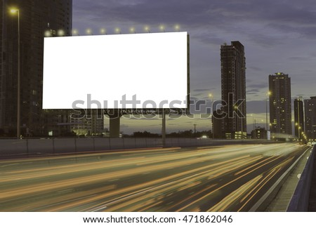 Blank billboard on the highway during the twilight with city background. With clipping path on screen.- can be used for display your products or promotional.