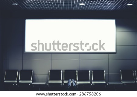 Blank billboard with clean space for publicity content or text message, advertising mock up in interior, public commercial board in waiting of airport hall with empty chairs, template banner indoors - stock photo