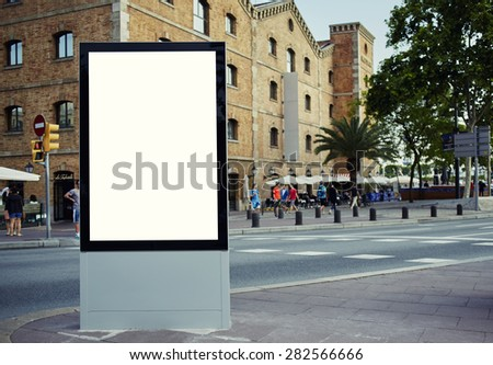 Blank billboard with copy space for your text message or content, public information board in the big town, advertising mock up empty banner in metropolitan city at beautiful sunny day - stock photo