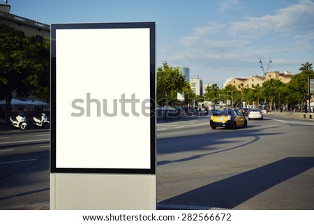 Blank billboard with copy space for your text message or content, public information board in the big city, advertising mock up empty banner in metropolitan city at beautiful sunny day - stock photo