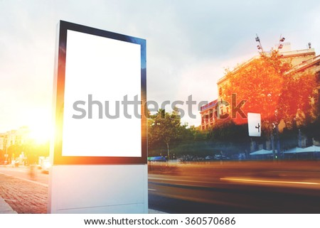 Blank billboard with copy space for your text message or promotional content, empty public information board in the big town, advertising mock up banner in metropolitan city in summer evening - stock photo