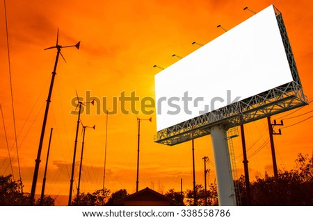Blank billboard  with wind turbine at sunset time for advertisement. - stock photo