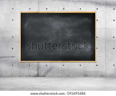 Blank Black Chalkboard on a Concrete Wall