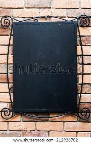 blank blackboard at a brick wall - nice background with space for text - stock photo