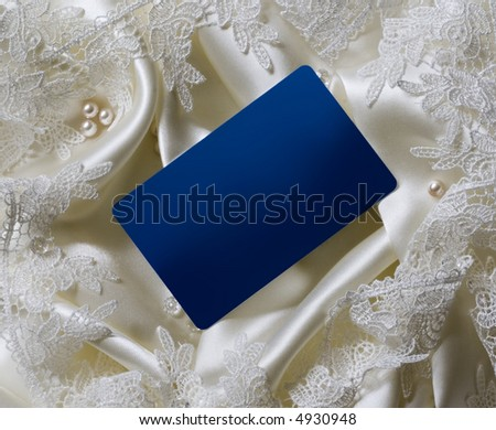 Blank blue card on white satin background with lace, pearls and beads - stock photo