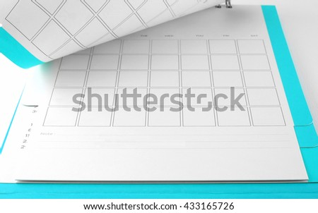 blank blue desk calendar with lines for notes on white background, flip the calendar page - stock photo