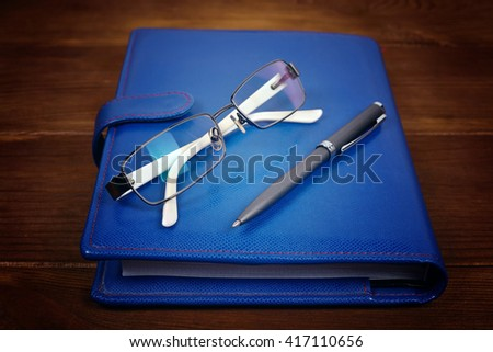 blank blue leather diary, glasses and pen on wooden desk - stock photo