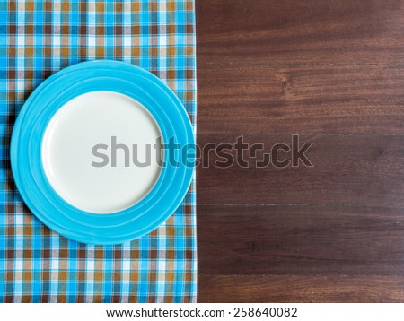 Blank blue plate on checked tablecloth over wooden table background - stock photo