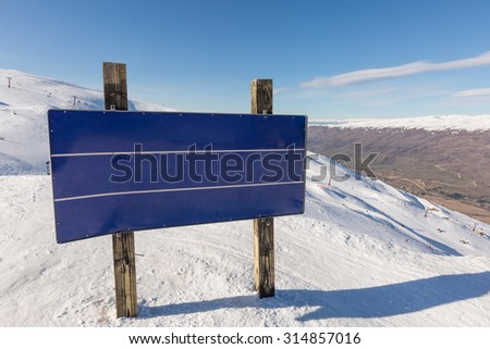 Blank Blue Road Sign with mountain and snow at the background - stock photo
