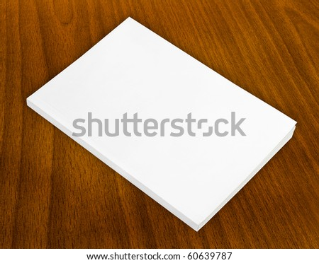 Blank book with white cover on wood background. - stock photo