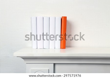 Blank books and orange one on shelf on white wallpaper background - stock photo