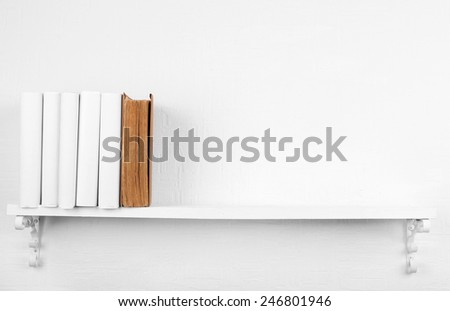 Blank books with brown one on bookshelf on white wall background - stock photo