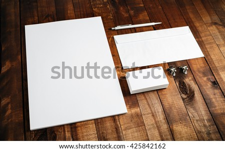 Blank brand template. Photo of blank stationery set on wooden table background. Mock-up for branding identity for design portfolios. Letterhead, business cards, envelope and pen. - stock photo