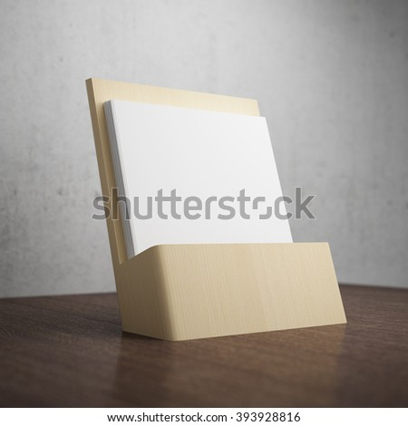 Blank brochure with wooden holder on table - stock photo