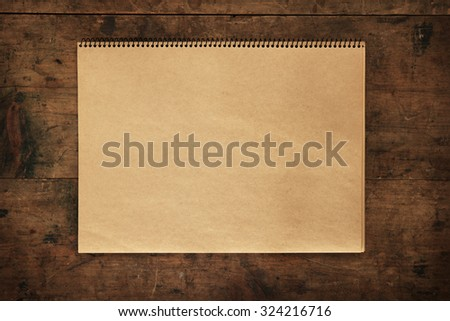 Blank brown paper scrap book on rustic retro table or wall. - stock photo