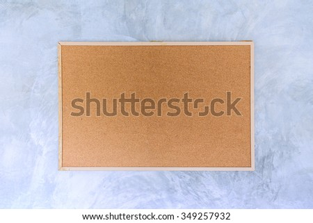 Blank bulletin board with wooden frame on cement wall.  - stock photo