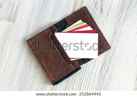 Blank business card. Conceptual composition with leather business-card folder, stack of colorful business cards and white blank business card on the foreground - stock photo