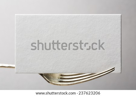 blank business card or invitation on fork - stock photo