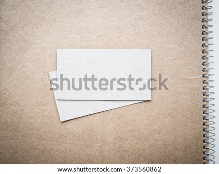 Blank business cards on kraft notebook cover, mockup