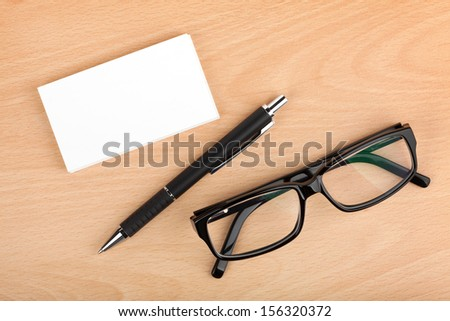 Blank business cards with pen and glasses on wooden office table - stock photo