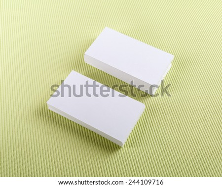Blank business cards with soft shadows on green background. - stock photo