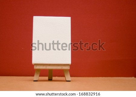 blank canvas in portrait position on mini easel.