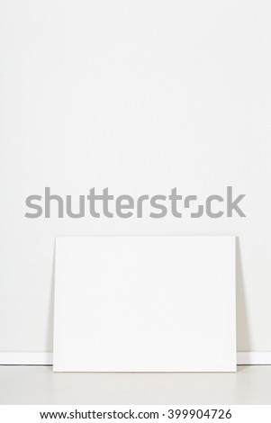 Blank canvas leaning against empty white wall