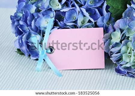 Blank card and flowers over with beautiful hydrangeas and room for your text. Shallow depth of field. - stock photo