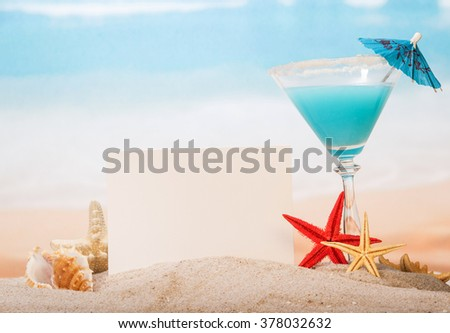 Blank card, cocktail and star in the sand on the seashore - stock photo