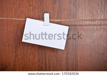 blank card on a rope on a wooden background