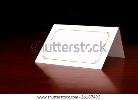 Blank card on dark timber table, with copy space. - stock photo