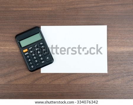 Blank card with calculator on wooden table - stock photo