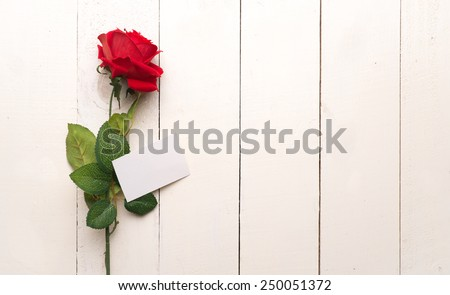 Blank card with red rose on a wooden background. Copy space. 8 march International woman day - stock photo