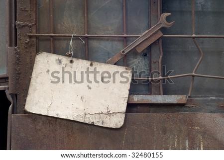 Blank cardboard sign in a  factory, free copy space, grunge - stock photo