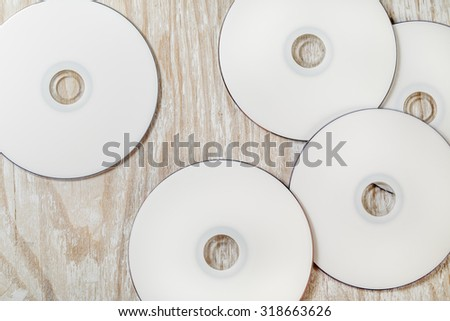 Blank CD and DVD on light wooden background. Top view. - stock photo