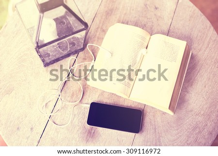 Blank cell phone, headphones and a book on the table - stock photo